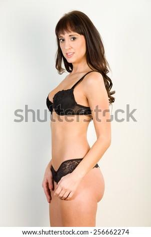 Model poses wearing black thong and matching bra - stock photo