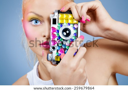 Model posing with bejeweled vintage photo camera. Focus on eye. - stock photo