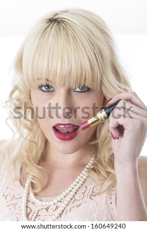Model Released. Attractive Young Woman Applying Lipstick