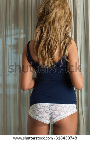 Model standing by curtains - stock photo