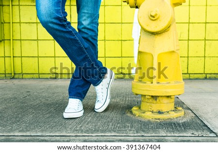 Model striking a pose on city side walk in blue jeans. (fashion/hipster concept) - stock photo