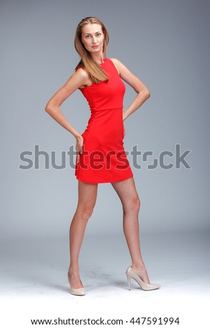 Model tests. Young gorgeous caucasian blonde in red dress posing over grey background - stock photo