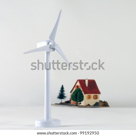 Model wind turbine with a house - stock photo