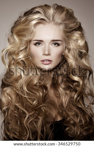 Model with blonde long hair. Waves Curls Hairstyle. Hair Salon. Updo. Fashion model with shiny hair. Woman with healthy hair girl with luxurious haircut. Hair loss Girl with hair volume. - stock photo