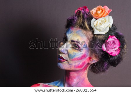 Model with colorful make-up and roses in hair - stock photo
