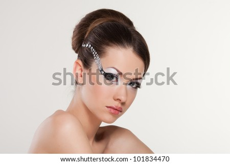 Model with creativity make-up with stylish hairstyle. Close-up portrait of young beautiful woman.