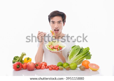 Model with Fruits and Vegetables-Cheerful young man eating healthy salad, fruits - stock photo