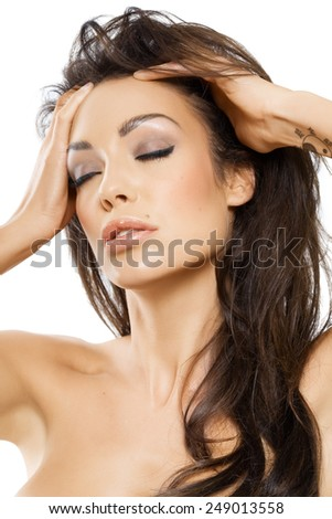 Model with her hands in hair and eyes closed.
