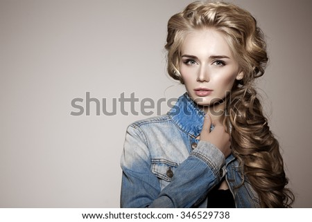Model with long braided hair. Waves Curls Braid Hairstyle. Hair Salon. Updo. Fashion shiny hair. Woman with healthy hair, girl with luxurious haircut. Hair loss, braiding hair volume, jeans, denim.  - stock photo
