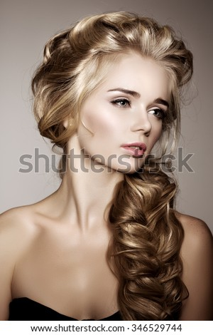 Model with long braided hair. Waves Curls Braid Hairstyle. Hair Salon. Updo. Fashion shiny hair. Woman with healthy hair, girl with luxurious haircut. Hair loss, braiding hair volume.  - stock photo