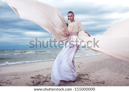 Model with long dress like a wings at the beach