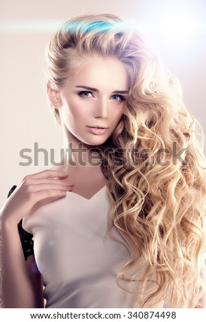 Model with long hair Blonde Waves Curls Hairstyle Hair Salon Updo Fashion model with shiny hair Woman with healthy hair girl with luxurious haircut Hair loss Girl with hair volume lights  - stock photo