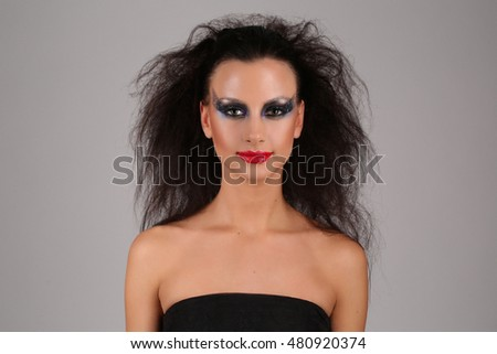 Model with makeup and wild hair. Close up. Gray background