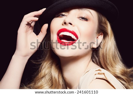 Model with red lips wearing black hat.