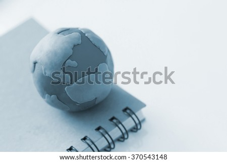 Modelling Clay of Globe on book - stock photo