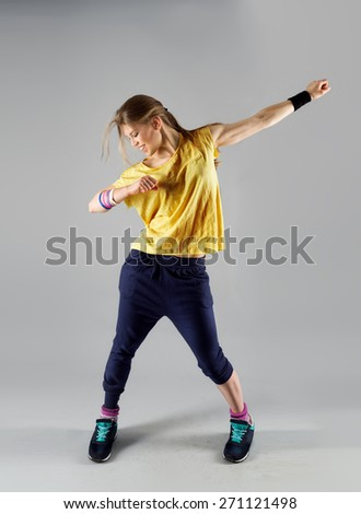 Modern active female artist dancing excited posing in studio. Sport, gym and fitness.  - stock photo