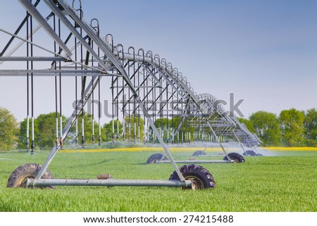Modern agricultural irrigation system spraying in wheat field - stock photo