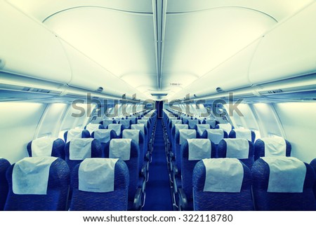 Modern Airplane seats in perspective. Transportation concept. Aircraft's corridor interior in modern tones. - stock photo