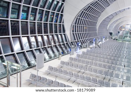 Modern airport lobby at night with empty chairs.