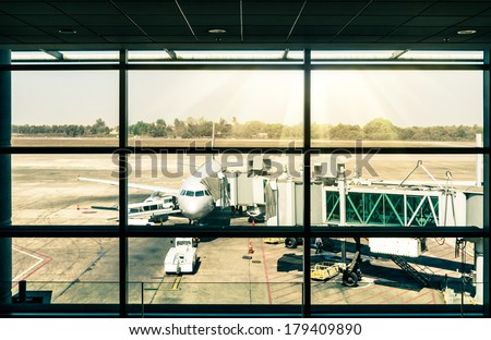 Modern airport with airplane at the terminal gate ready for takeoff - stock photo