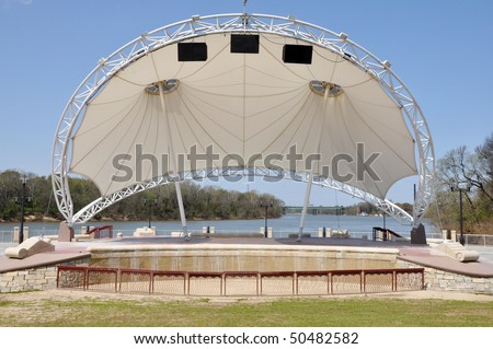 Modern amphitheater stage beside river at city park. - stock photo