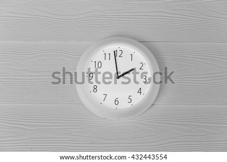 Modern analog wall clock isolate on wood background. - stock photo