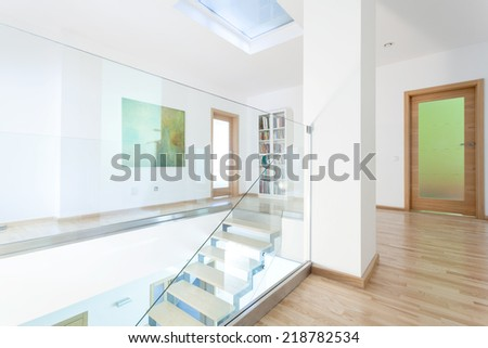 Modern and bright hallway with glass staircase, horizontal - stock photo