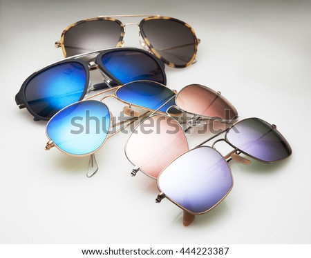 modern and classic sunglasses with mirrored lenses on a gradient background