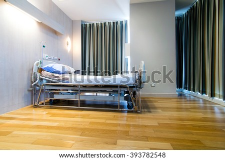 modern and comfortable equipped hospital room with an empty bed, closed curtain  - stock photo