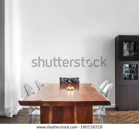 Modern and Contemporary dining room table and decorations with blank wall for your text, image or logo. - stock photo