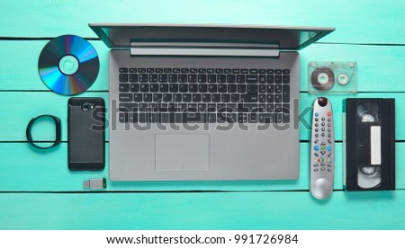 Modern and obsolete devices and gadgets on a turquoise wooden table. Laptop, audio and video cassette, smartphone, remote control, CDs, USB flash drive, smart bracelet.Digital and analog technologies.