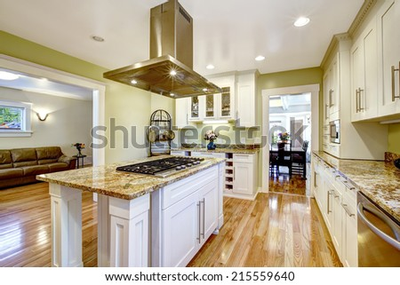 Modern and practical kitchen room design. White cabinet with granite tops, kitchen island with built-in stove and steel hood - stock photo