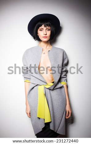 modern and sexy woman in a fashion outfit with black hat on gray wall - stock photo