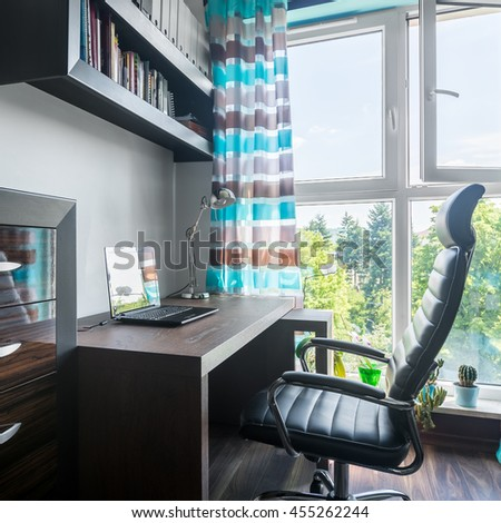 Modern and small workspace near big window with brown wooden furniture and comfortable armchair