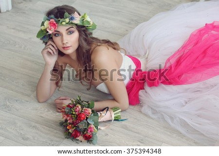 Modern and stylish bride in a floral wreath on her head and with a beautiful wedding bouquet - stock photo