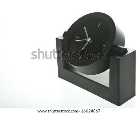 Modern and stylish desk clock in black with silver hands on a white background.