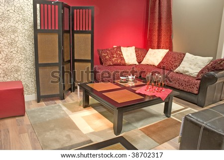Modern and stylish dining room with sofa and table. Luxurious cushions. Red toned walls and dressing screen.