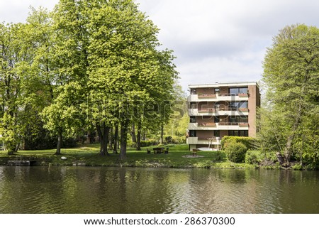 Modern apartment building at a river - stock photo
