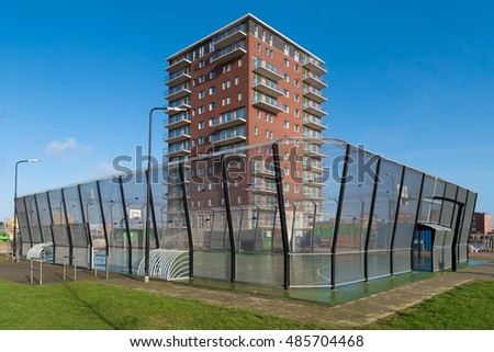 modern apartment building with kids playground surrounded by a large fence
