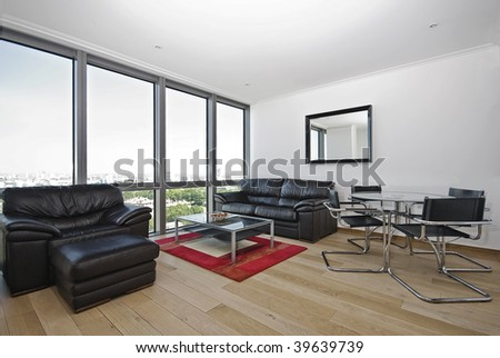 modern apartment with floor to ceiling windows and leather sofas