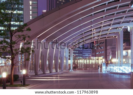modern architecture outdoor pathway under arc glass roof in the night - stock photo