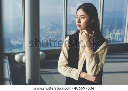 Modern Asian woman entrepreneur is thinking about the future of an important contract signing with investors, while is looking in skyscraper window on a city view during her business trip to China - stock photo