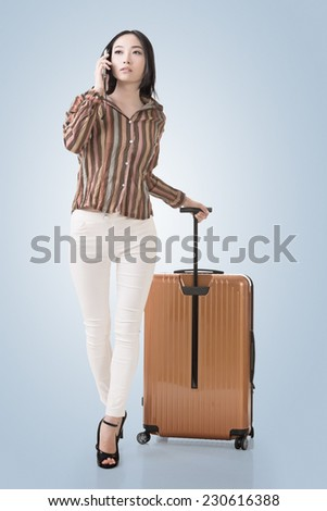 Modern Asian woman talking on cellphone and walking and holding a suitcase. - stock photo