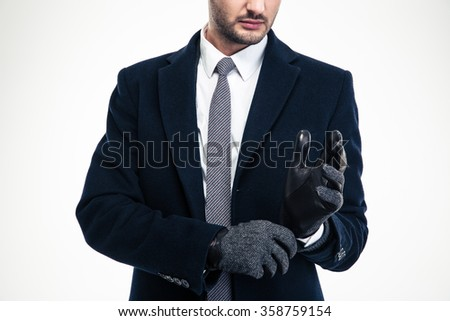 Modern attractive businessman in classic suit wearing fashionable gloves isolated over white background - stock photo