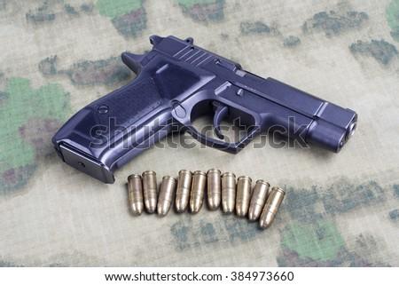 modern automatic pistol on camouflage background - stock photo