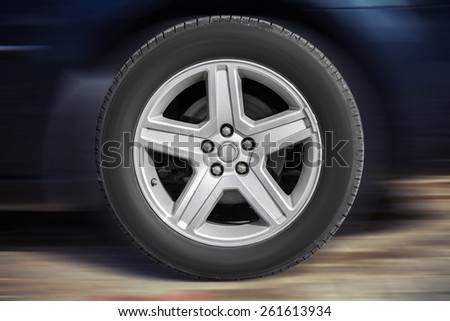 Modern automotive wheel on light alloy disc with blurred car background