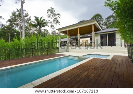 Modern backyard with swimming pool and outdoor entertaining area in Australian mansion - stock photo