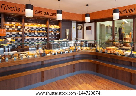 Modern bakery interior with glass display counters full of scrumptious bread and pastries - stock photo