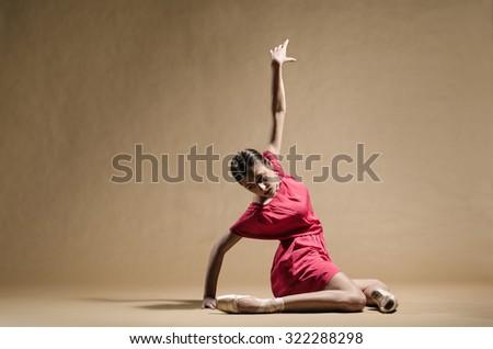 Modern ballerina in red dress posing in studio. - stock photo