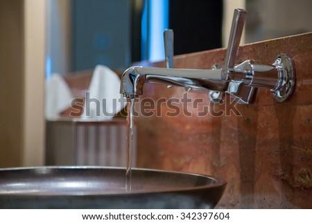 Modern bathroom faucet - stock photo
